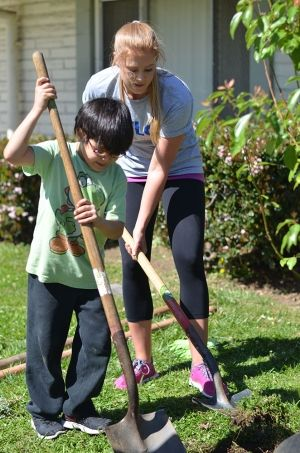 Lauren Wood shoveling with child at Los Angeles Trial Lawyers' Charity Event